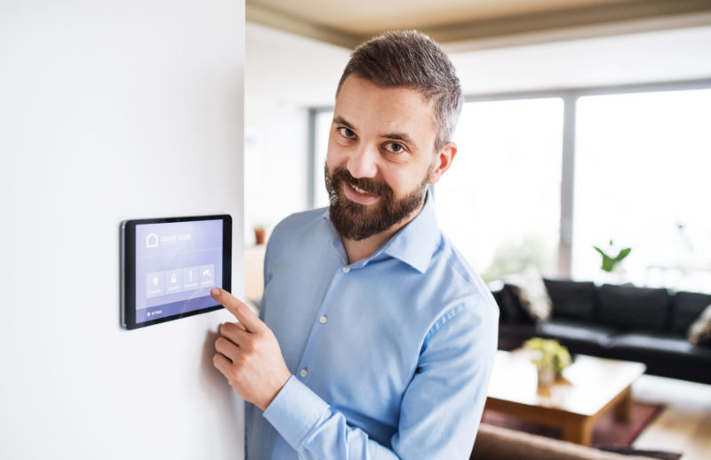 A Man Pointing To A Tablet With Smart Home Screen.