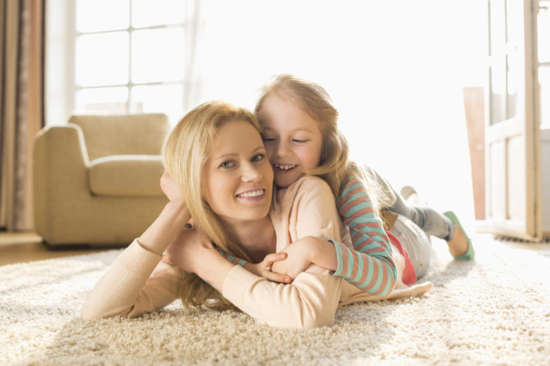 Portrait Of Happy Mother With Daughter Lying On Floor At Home